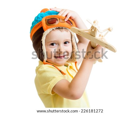 kid boy playing with wooden airplane toy and dreaming about pilot profession - stock photo