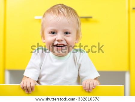 Kid boy sitting inside yellow opened kitchen box - stock photo
