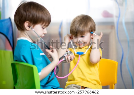kid boy weared as doctor role playing with his younger brother - stock photo