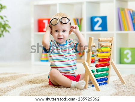 kid boy with eyeglasses playing abacus toy - stock photo