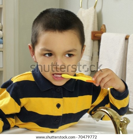 Kid brushing teeth in front of a mirror, Hispanic, four years old - stock photo