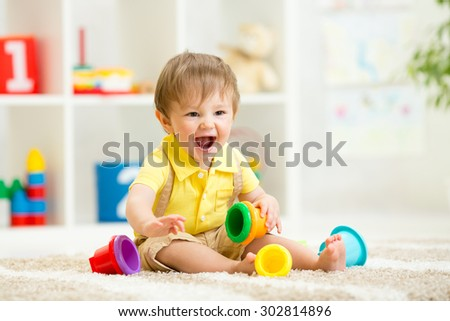 kid child girl playing on floor at home or kindergarten - stock photo