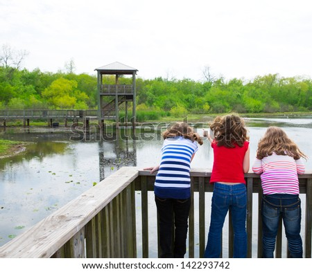 kid children girls looking and pointing at park lake in Texas rear view - stock photo