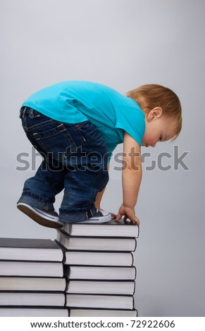 Kid climbing on top of the books pile describing education efforts - stock photo