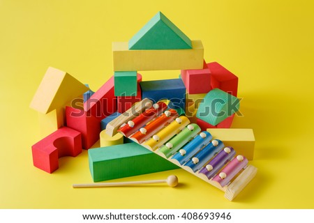 Kid creative play. Building blocks and xillophone on bright background - stock photo
