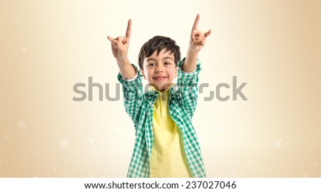 Kid doing the horn sign over ocher background