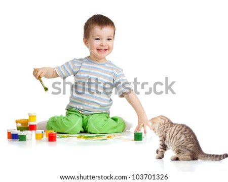 kid drawing with paints and playing with kitten