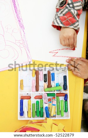 Kid  draws on a white sheet with crayons
