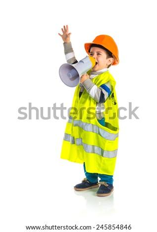 Kid dressed like workman shouting by megaphone - stock photo