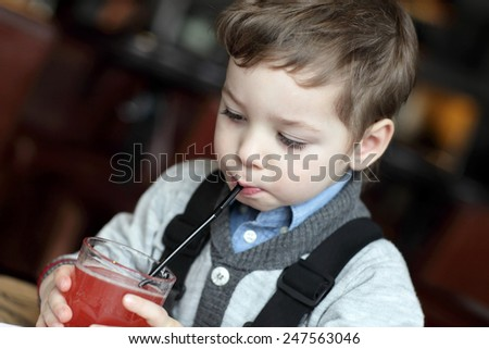Kid drinking red juice in the cafe - stock photo
