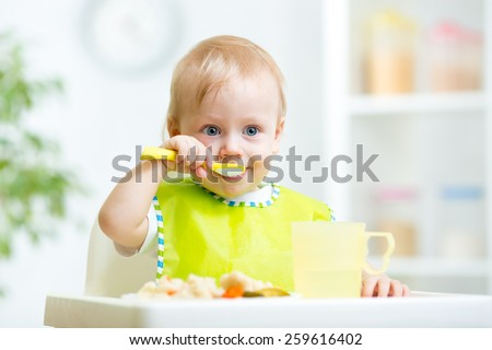 kid eating healthy food with a spoon at kitchen