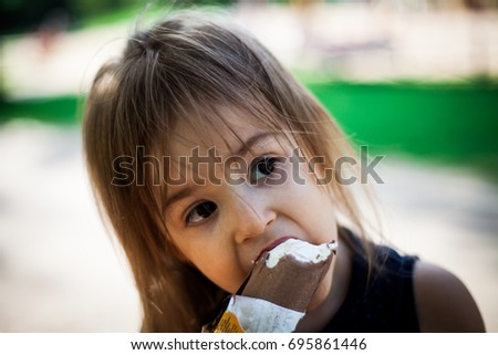 Kid eating ice-cream in a park