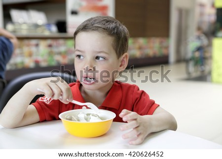 Kid eating meat dumplings with sour cream in cafe - stock photo