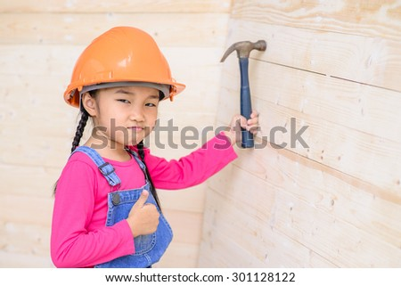 Kid engineer on carpenter work thumb with hammer