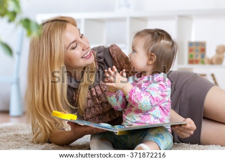 kid girl and mother read a book indoors - stock photo
