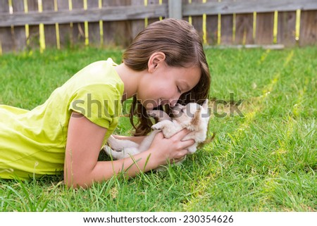 kid girl and puppy dog happy playing with chihuahua  pet lying in backyard lawn - stock photo