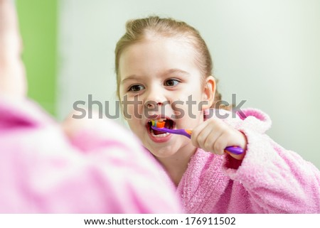 kid girl brushing teeth in bathroom - stock photo