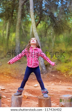 kid girl climbing tree trunks with open arms having fun in the pine forest - stock photo