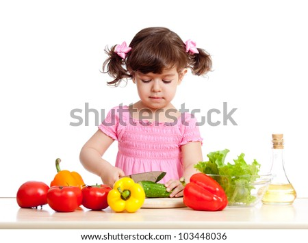 Kid girl cutting cucumber for salad. Concept healthy food. - stock photo