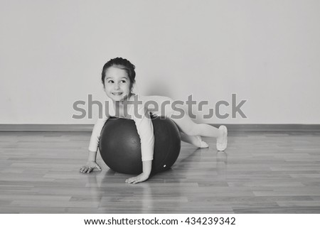 kid girl doing gymnastic exercises  on the fitball