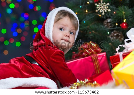 kid girl dressed as Santa Claus near Christmas tree with gifts - stock photo