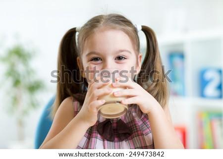 kid girl drinking milk or yogurt  from glass - stock photo