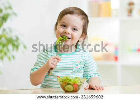 kid girl eating healthy vegetables at kitchen - stock photo