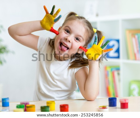 Kid girl having fun at home, her palms covered with paint - stock photo