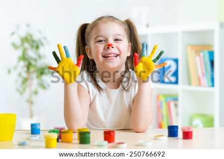 Kid girl having fun, her palms covered with paint - stock photo