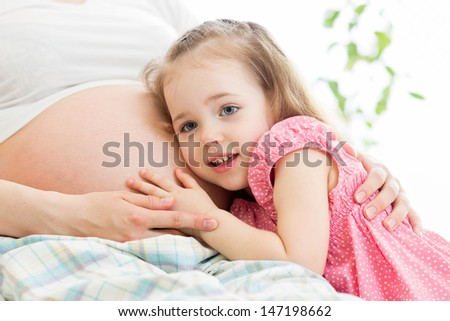kid girl listening pregnant mother's belly - stock photo