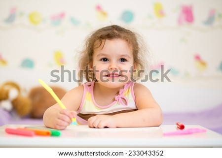 kid girl paints in her nursery at home - stock photo