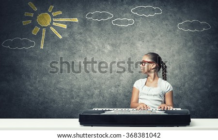 Kid girl play synthesizer - stock photo