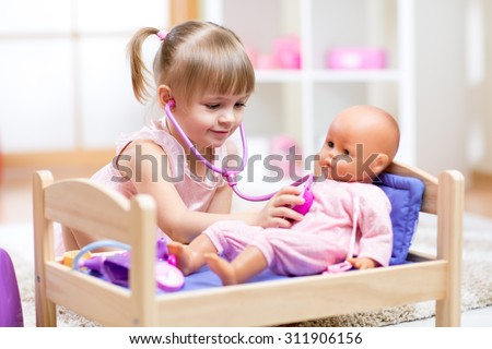 kid girl playing a doctor with doll in kindergarten - stock photo