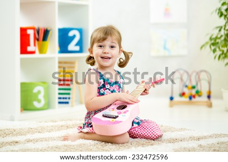 kid girl playing guitar toy at home - stock photo