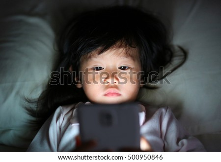 Kid girl playing smartphone lying on a bed at night
