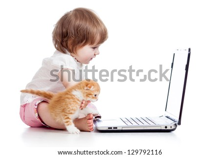 kid girl playing with kitten and laptop - stock photo