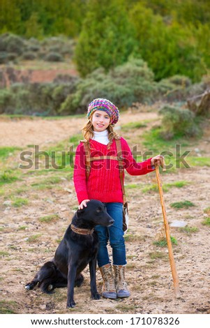 Kid girl shepherdess happy with dog flock of sheep and wooden stick in Spain - stock photo