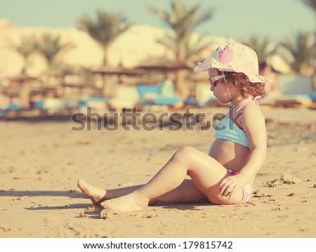 Kid girl sitting on the beach sand and sunbathing. Instagram effect - stock photo