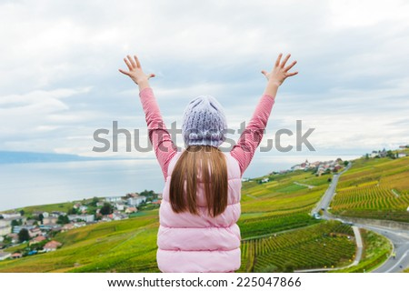 Kid girl stand between Lavaux vineyards looking at the view with arms open - stock photo