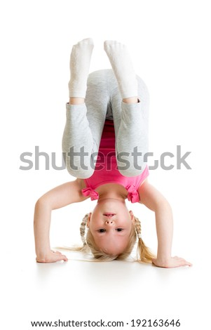kid girl standing head over heels and smiling, isolated on white background - stock photo