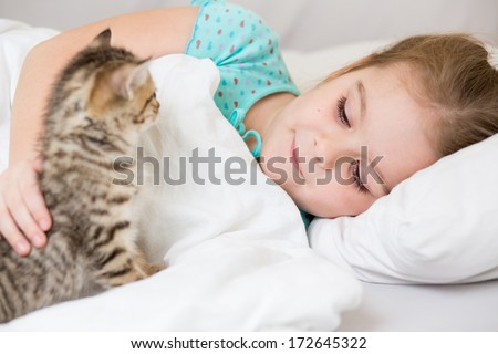 Kid girl with kitten laying in the bed - stock photo