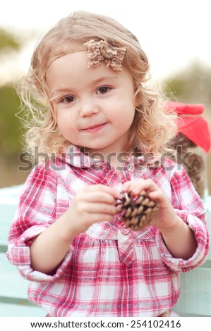 Kid girl 3-4 year old playing with fir cones outdoors. Looking at camera. Childhood.  - stock photo
