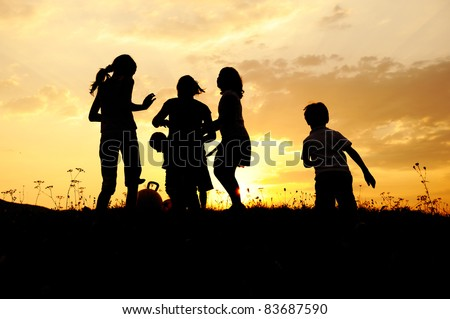 Kid group playing on meadow, sunset, summertime