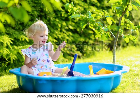 Kid having fun at summertime. Happy little child, adorable blonde toddler girl having fun playing outdoors in the garden with plastic toys sitting in blue sand box on a sunny summer day - stock photo