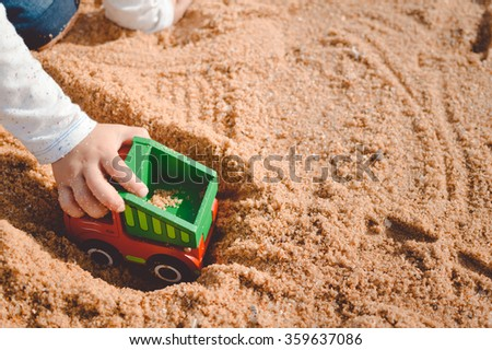 Kid having fun. Child playing with his truck toy on a sunny summer day sandy background.  - stock photo