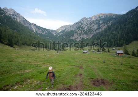 kid hiking in alps with high mountains in background - stock photo
