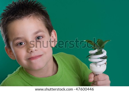 Kid holding a compact fluorescent bulb with a leaf. Global wamring concept. On green backdrop - stock photo