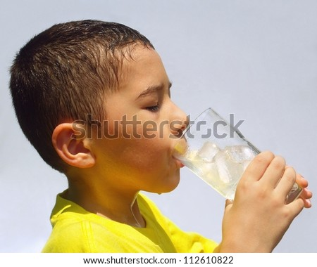 Kid hot and sweaty drinking a cold glass of iced lemonade under bright afternoon sunlight - stock photo