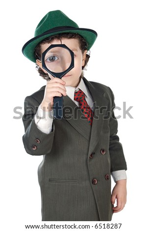 Kid in a suit with a magnifying glass - stock photo