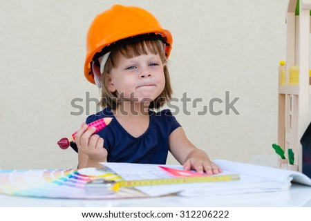 Kid in construction helmet pretending to be an architect - Construction, Architecture,  Home Improvement and Childhood concept - cute little girl in protective helmet - playing engineer /builder  - stock photo